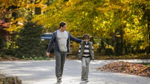 A man and a boy walking down a road