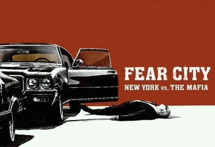 "Movie graphic of two cars parked, one with a driver's side door open and a man's body laying on the ground. The red back drop has the words ""Fear City: New York vs. The Mafia"