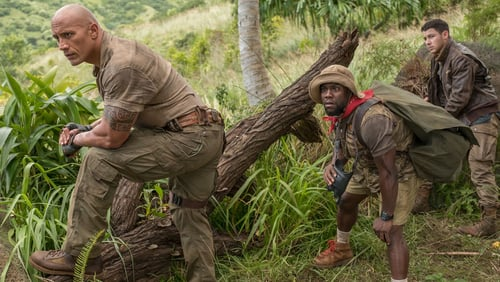 Three men crouching behind a log in the jungle