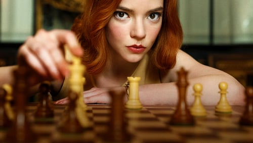 A woman leaning over a chess board, staring intently into the camera