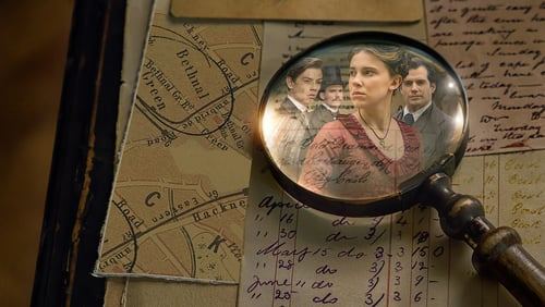 A magnifying glass on a table, the reflection of a young woman and three men can be seen in it