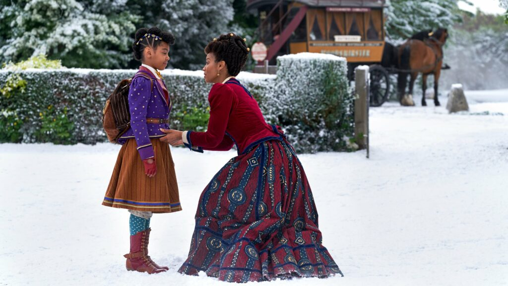 A woman and a young girl standing in the snow