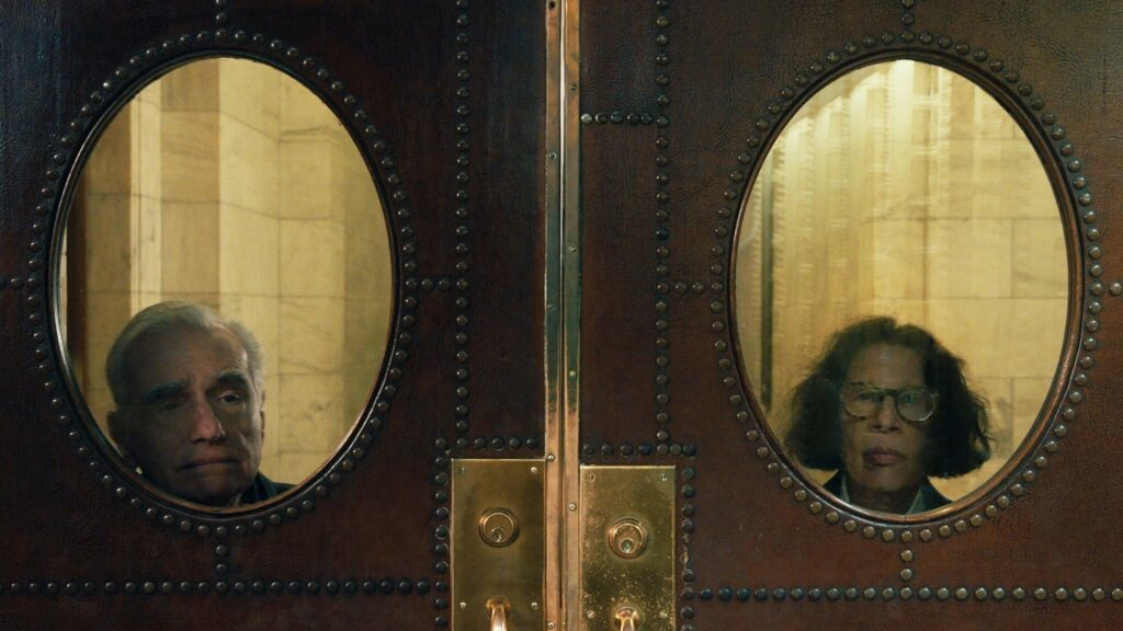 a double door with a oval window on each. a man looking through one window and a woman looking through the other