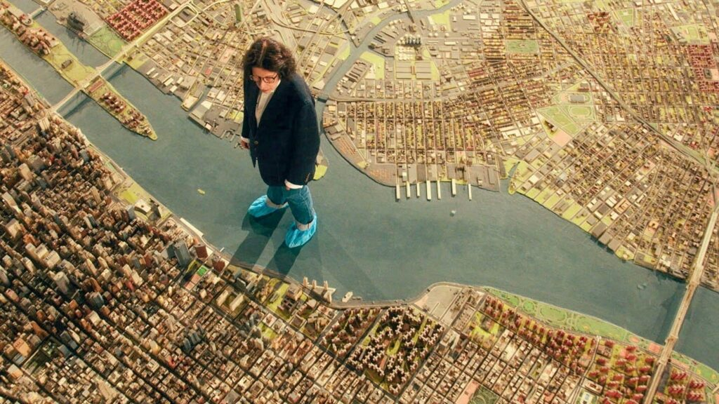 A woman standing in the middle of a model of the city of New York