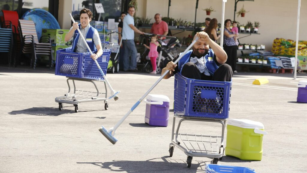 Two men, sitting in shopping carts, racing in a parking lot