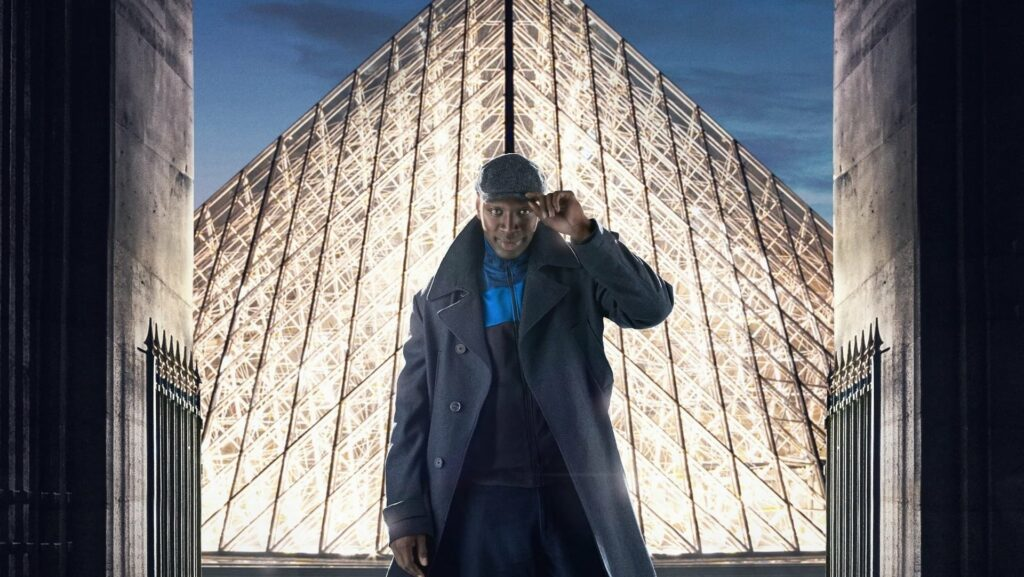 A man, in a cap and wool coat, standing in front of The Louvre