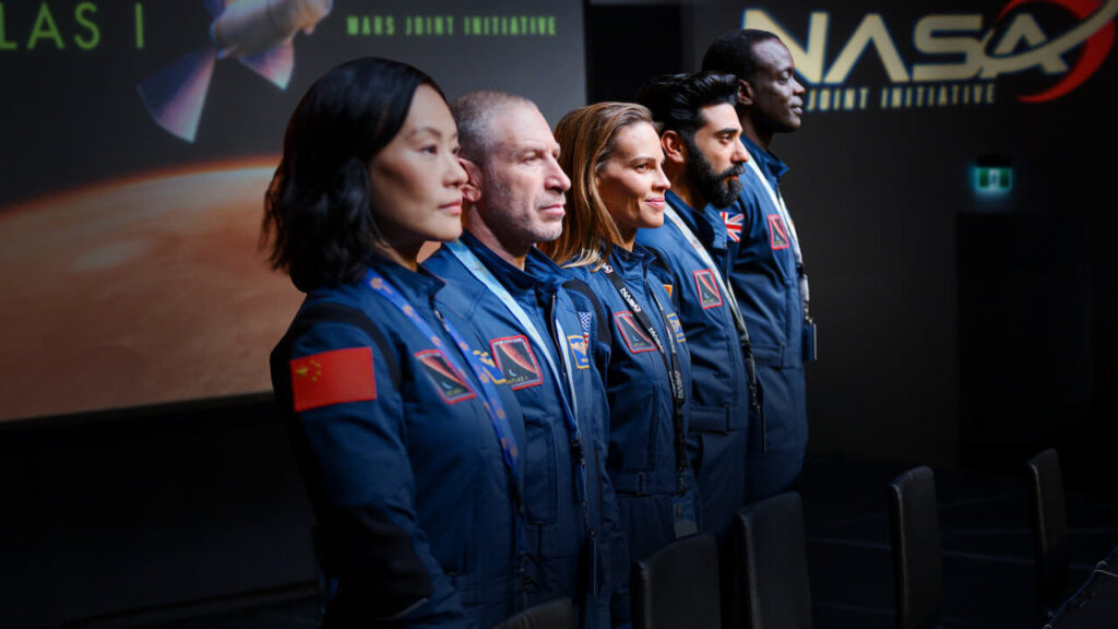 Five astronauts standing in a row