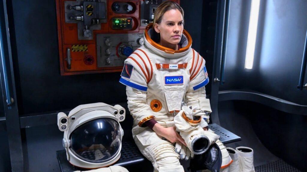 A female astronaut sitting alone in full space walking gear