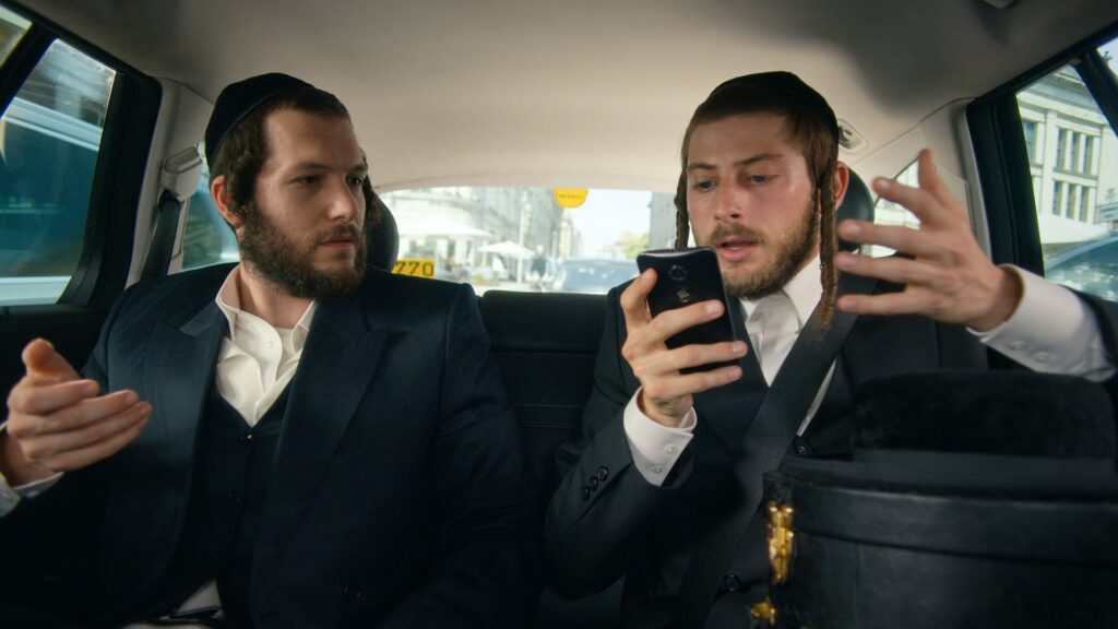 Two orthodox Jewish men sitting in the back of a taxi