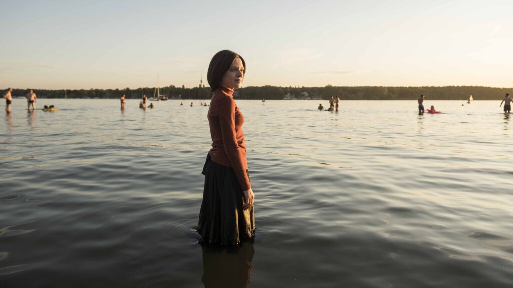 A young woman, standing knee deep in a lake, fully clothed