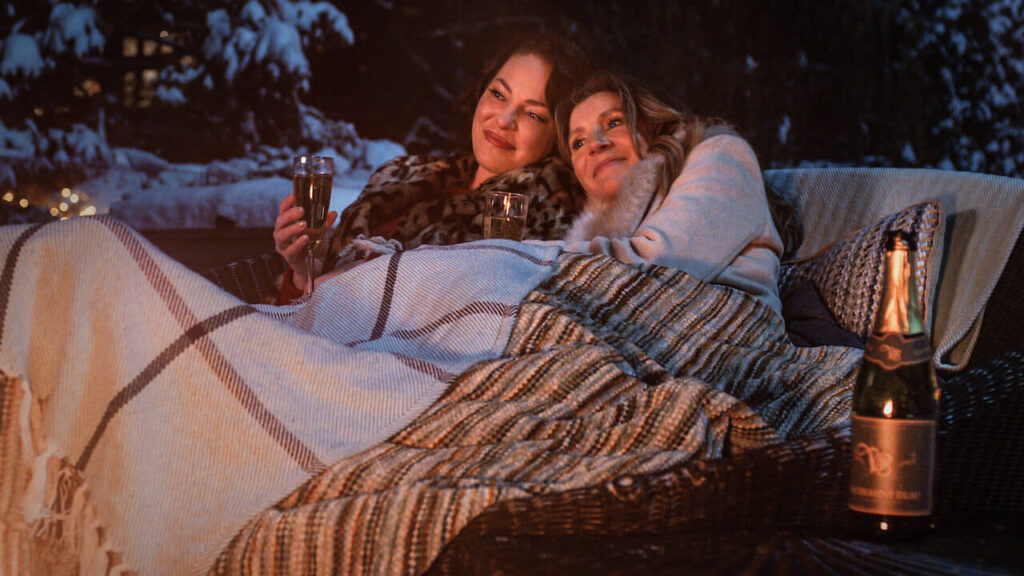 Two women sitting together, wrapped on blankets, drinking wine