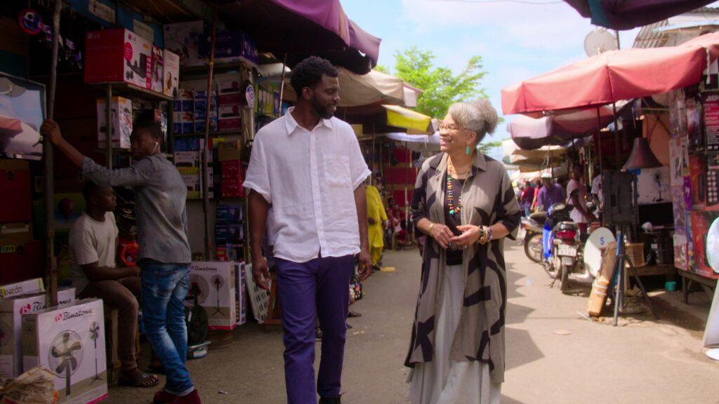 A man and a woman walking through an outdoor market