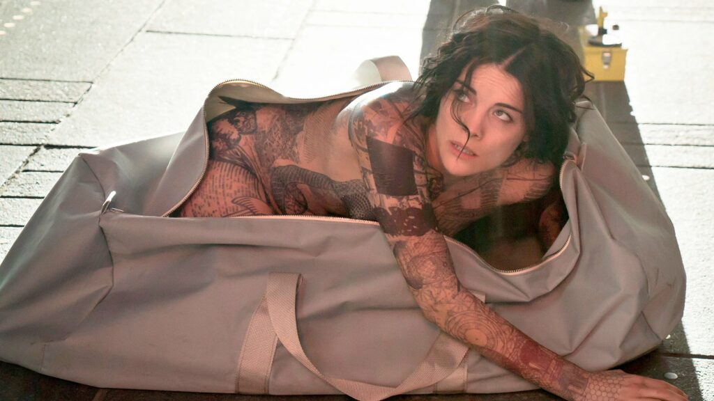 A heavily tattooed, naked woman crawling out of an oversized dufflebag