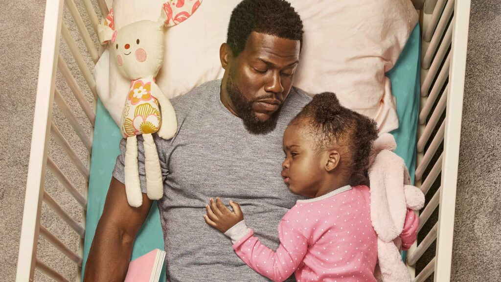 A dad asleep in a crib with his baby daughter