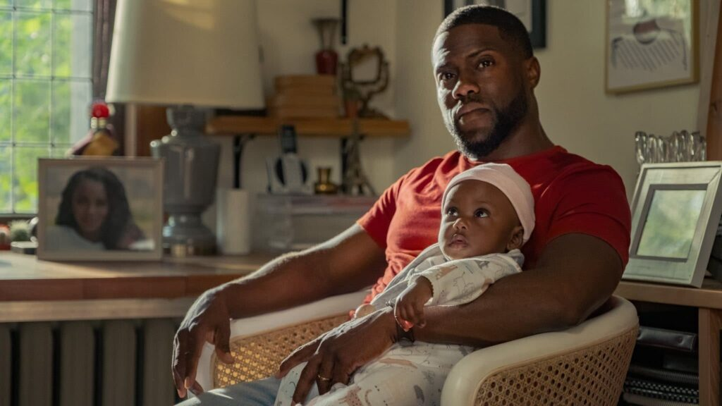 A dad sitting in a chair holding his infant daughter
