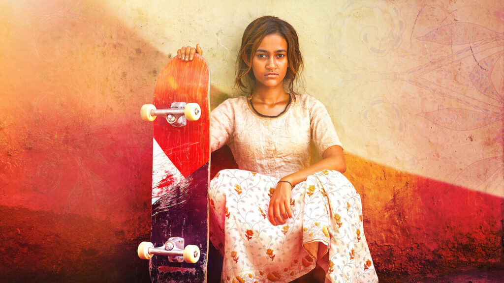 A young Indian girl, sitting by a wall holding a skateboard