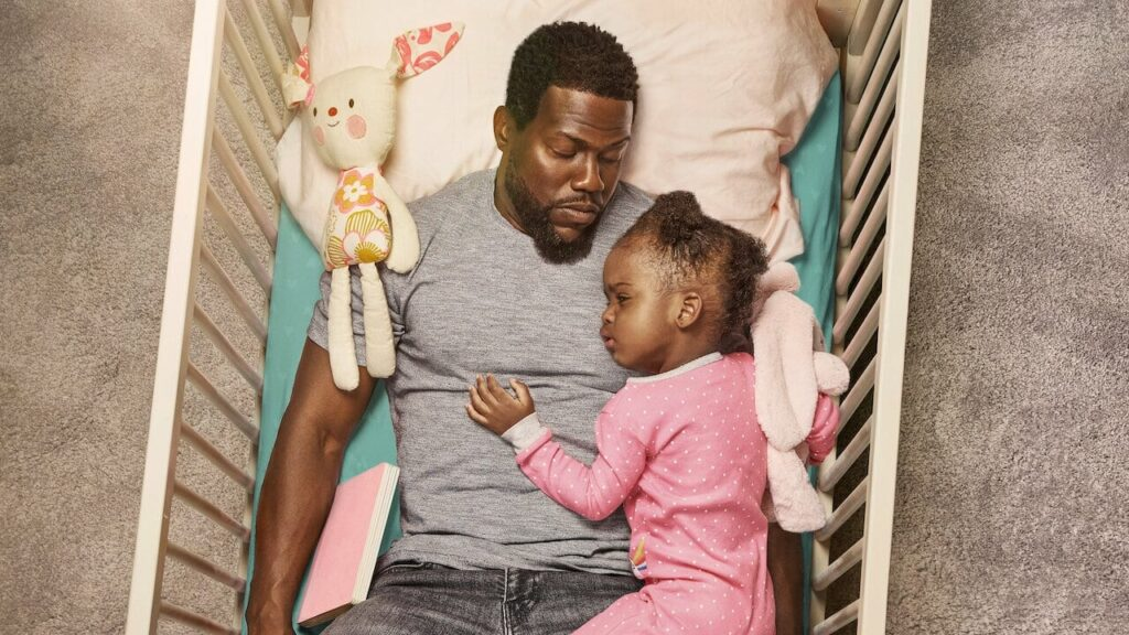 A father sleeping in a crib with his infant daughter asleep on his chest