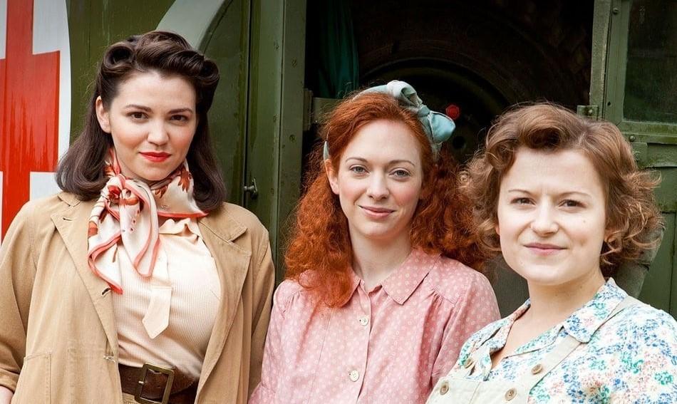 Three women, in 1940s attire, standing beside a war ambulance