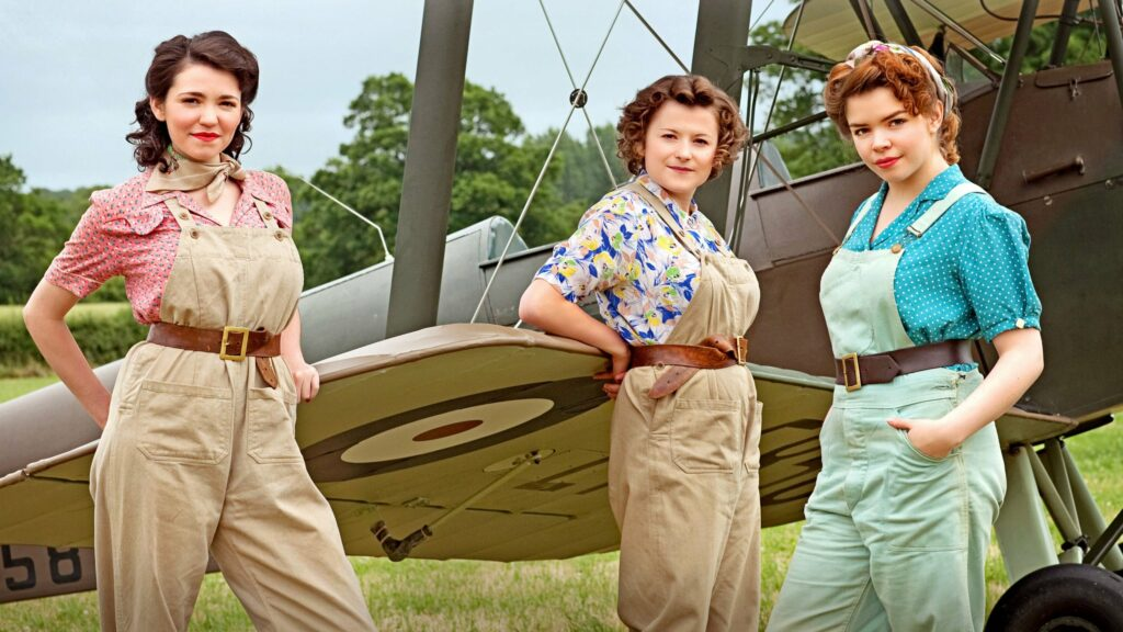 Three woman, in 1940s attire standing beside an airplane