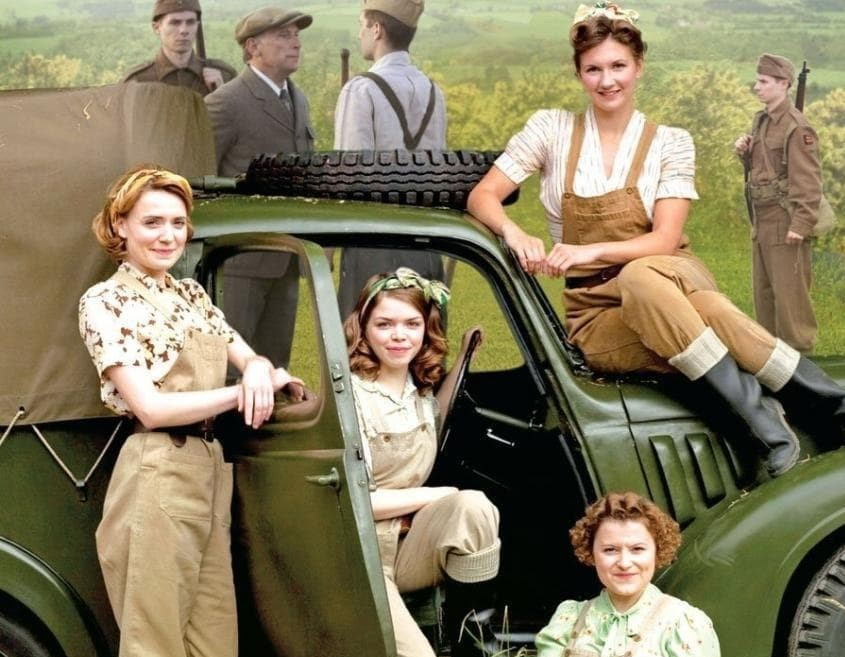 Four women, in 1940s attire, standing beside a military truck