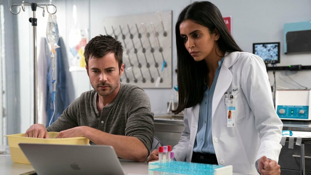 A man and a woman in a medical lab looking at a computer