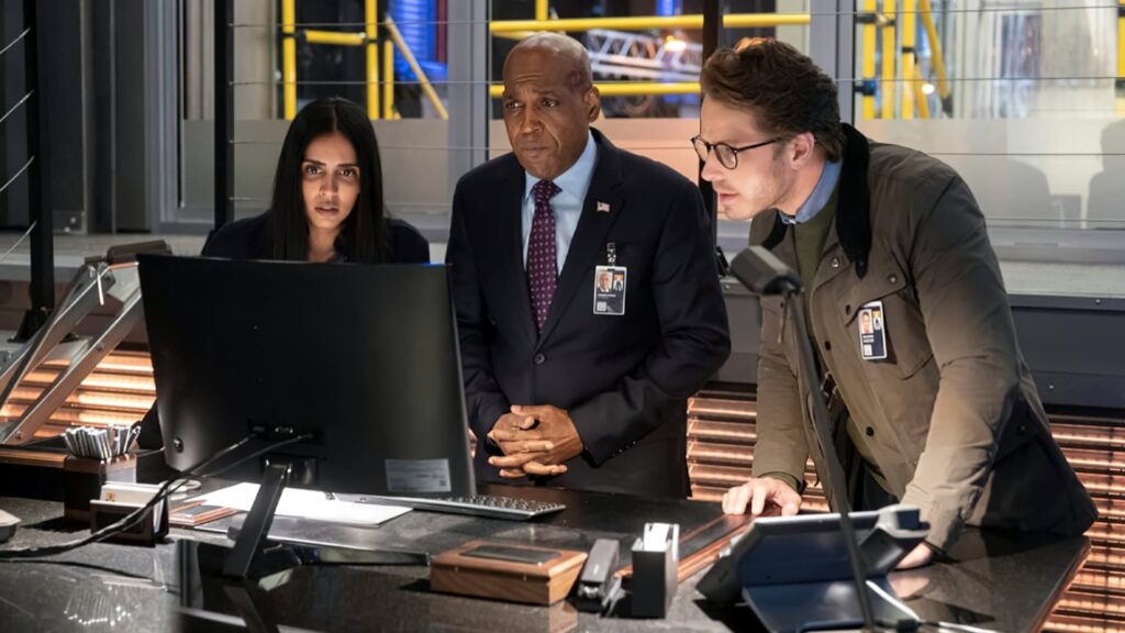 Two men and a woman looking at a computer screen in a police office