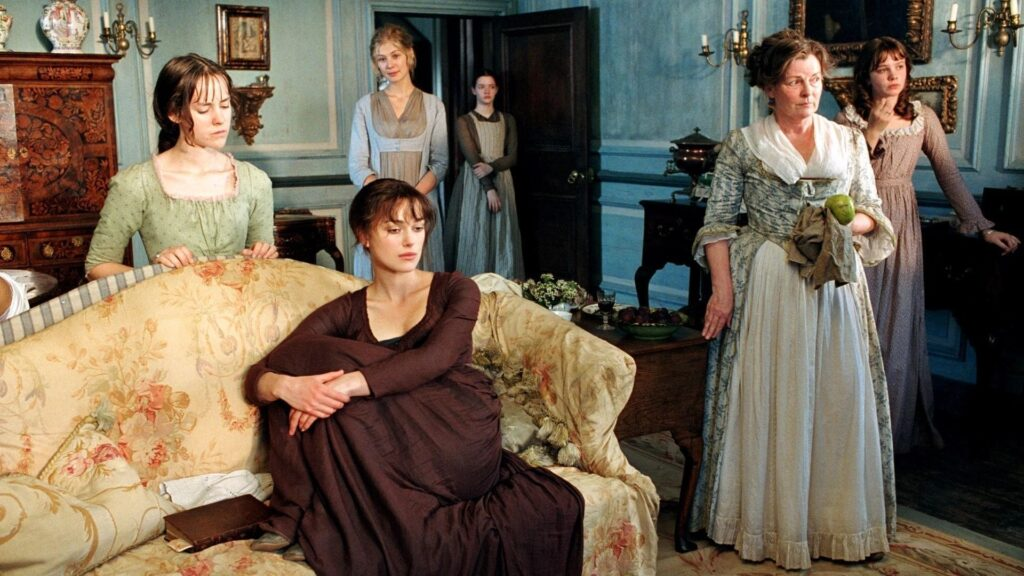 Six women, sitting and standing in a well appointed 19th century sitting room