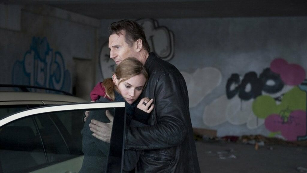 A man, hugging a woman in a parking garage
