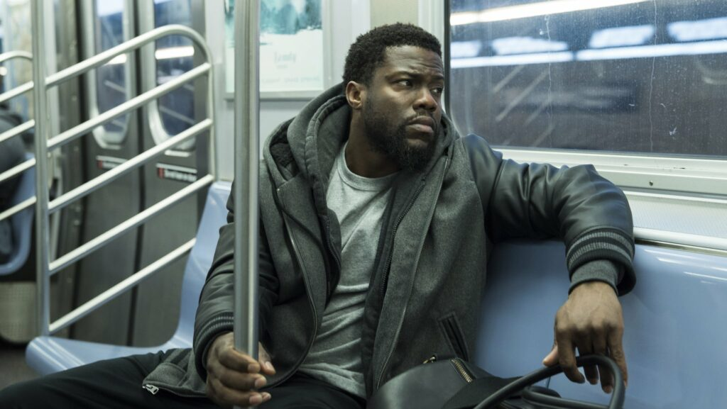 A man sitting on a subway, looking upset