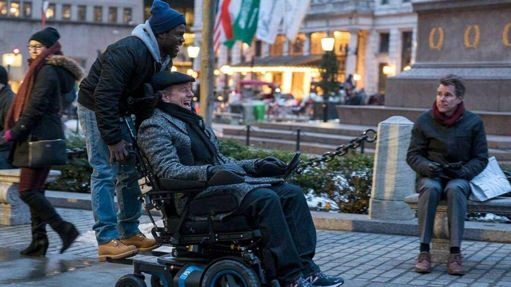 A man riding on the back of the electric wheelchair of his friend - both are laughing
