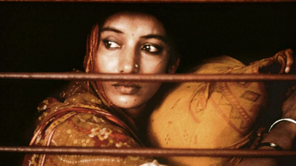 An Indian woman staring out of a train car window