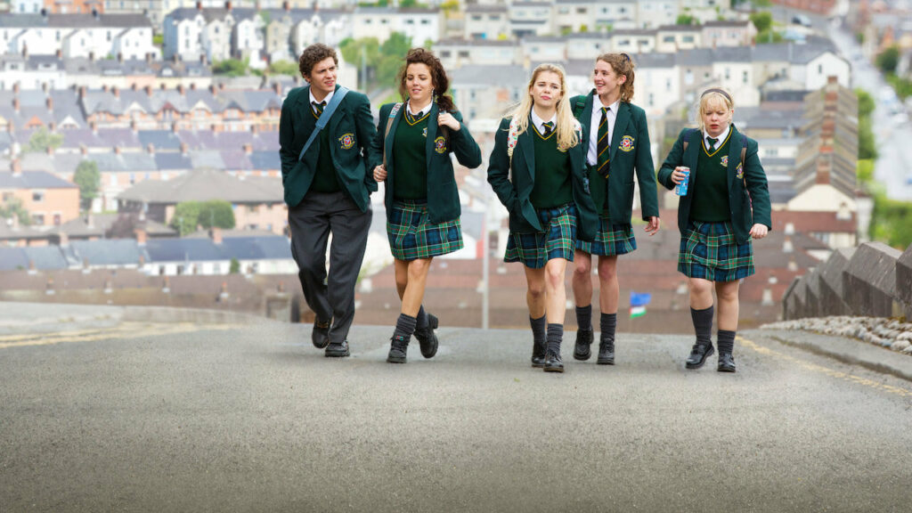 Four teen girls and a teen boy, wearing school uniforms walking down a street