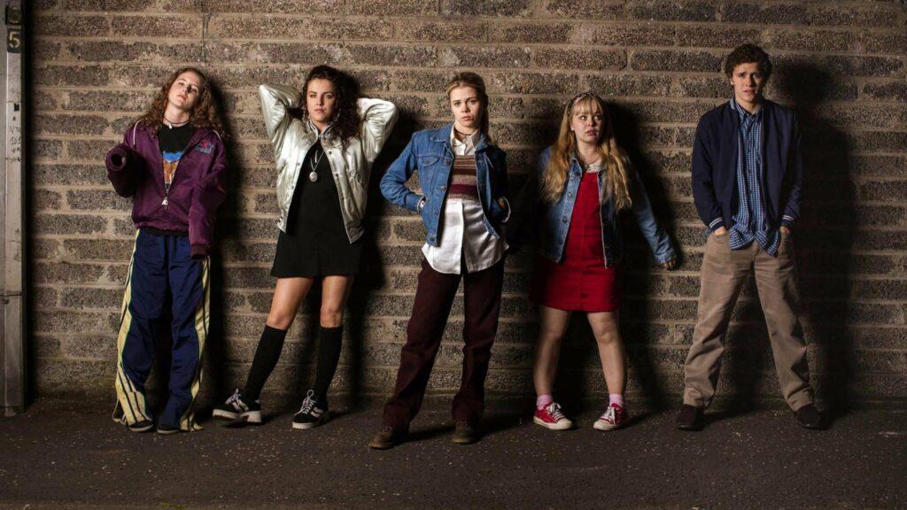 Four teen girls and a teen boy standing against an alley wall