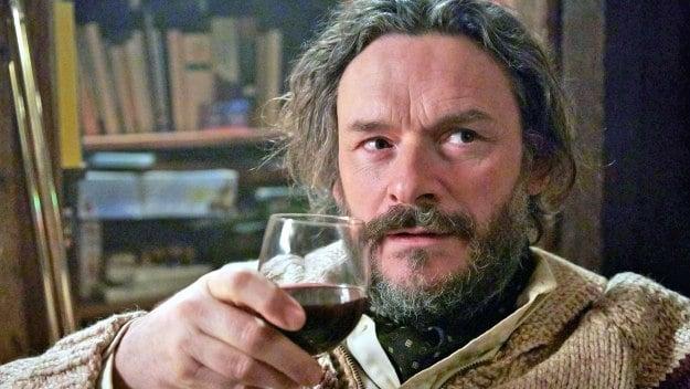 A scruff man, drinking a glass of wine