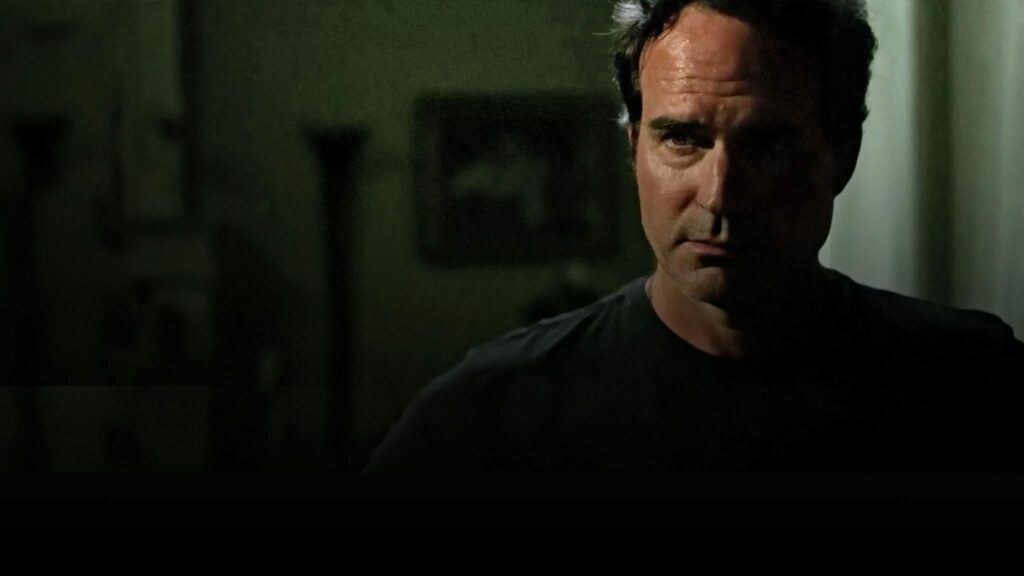 A man, in a darkened room