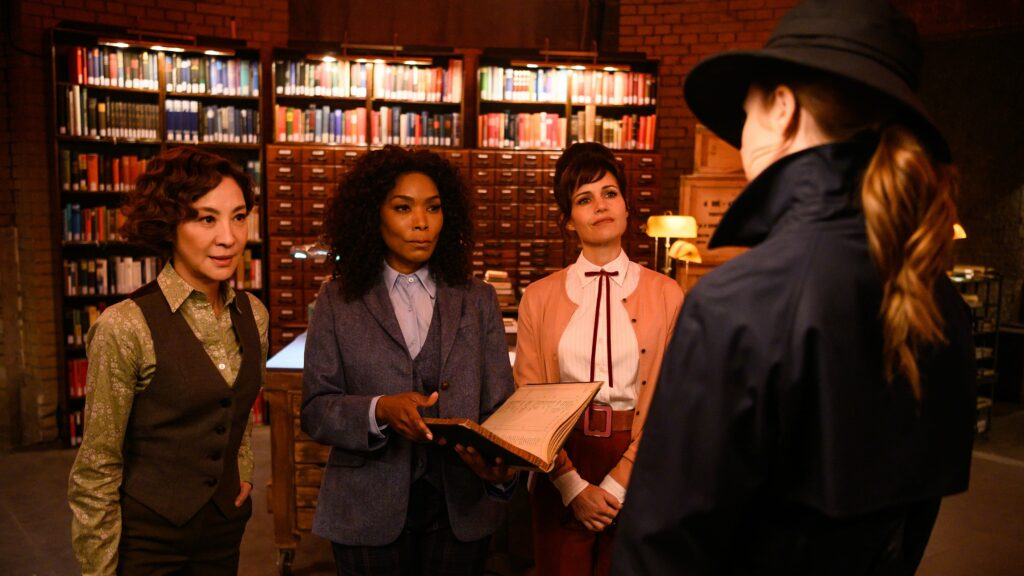 Four women standing in an elegant library