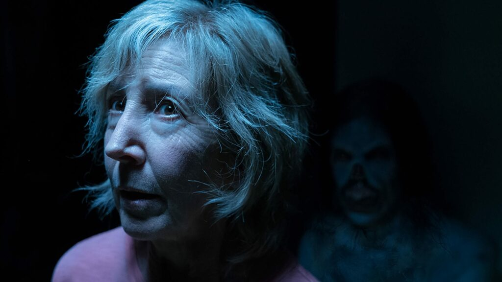 An older woman in the foreground with a creepy dude lurking in the background