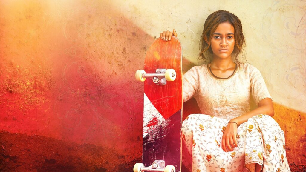 A young Indian girl sitting by a wall with a skateboard