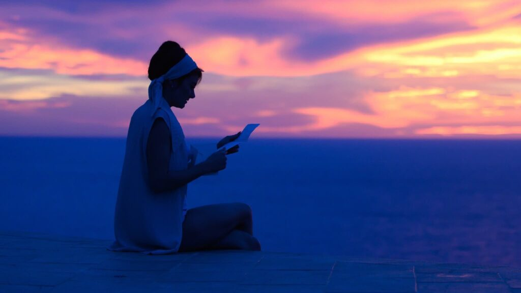 a woman sitting on a beach at sunset reading a letter