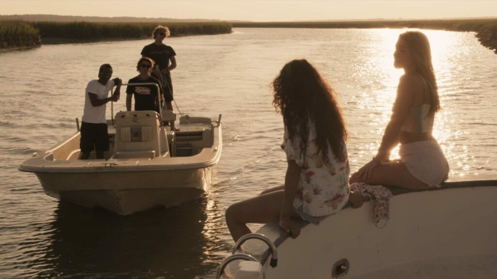 three teen guys on one boat and two teen girls on another boat