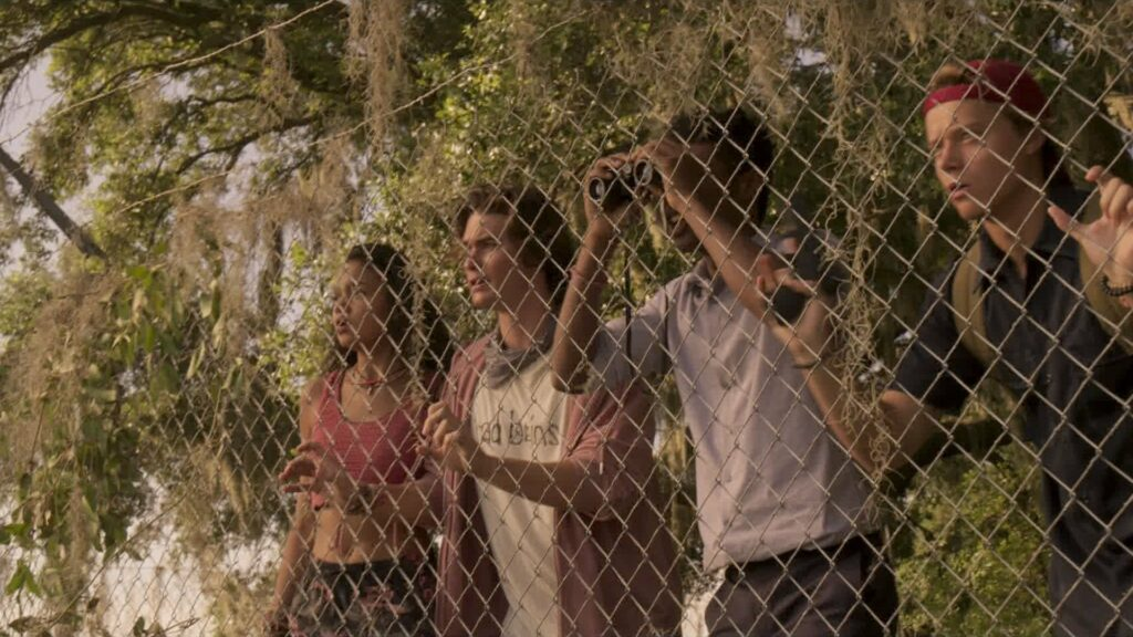 Four teens standing behind a fence looking in the distance