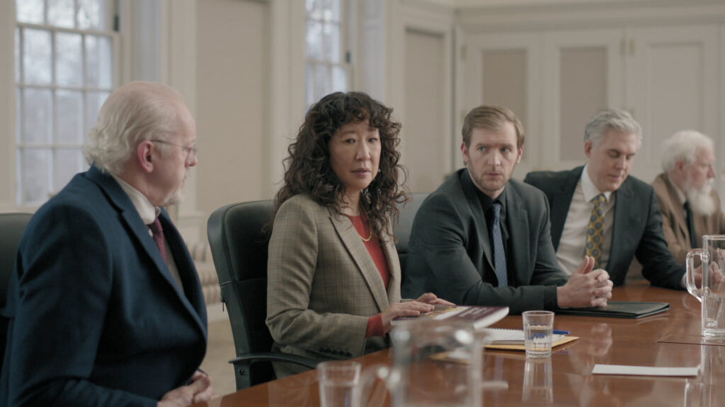A lone woman siting at a boardroom table with several men