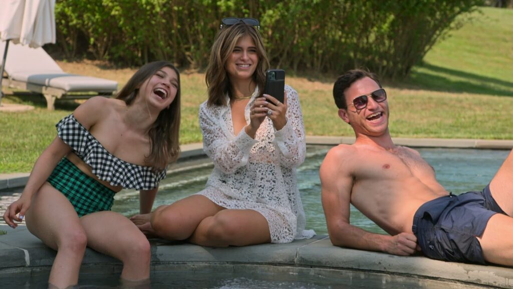 Three people sitting beside a pool laughing.