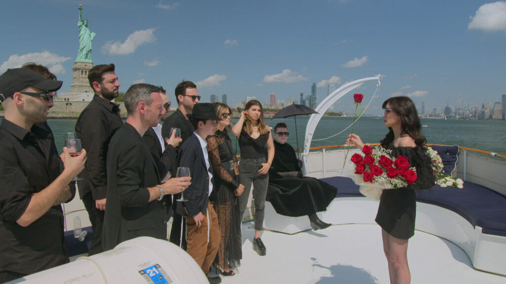 A woman standing on the deck of a yacht, holding an armful of red roses. There is a crowd of people standing on the deck with her.