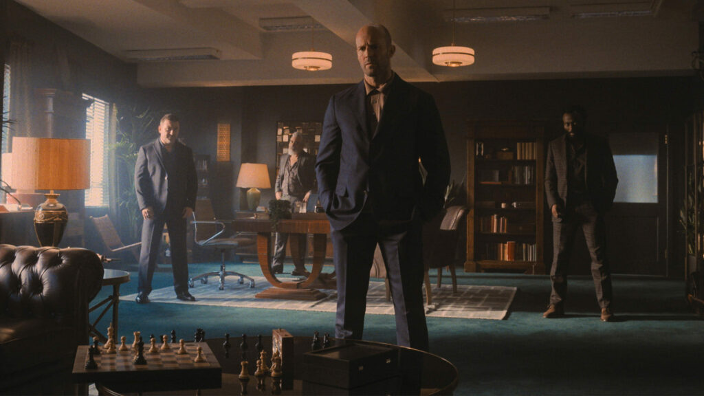 One man standing in an office, with a chess board in front of him, three men are standing behind him