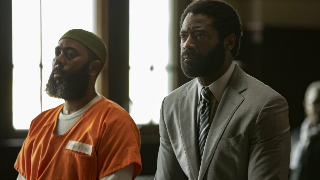 Two black men standing in a courtroom - one a prisoner the other his advocate