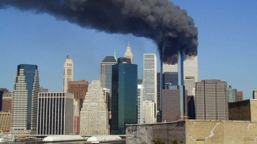 The Twin Towers still standing but fires blazing in both with black smoke billowing out of both buildings