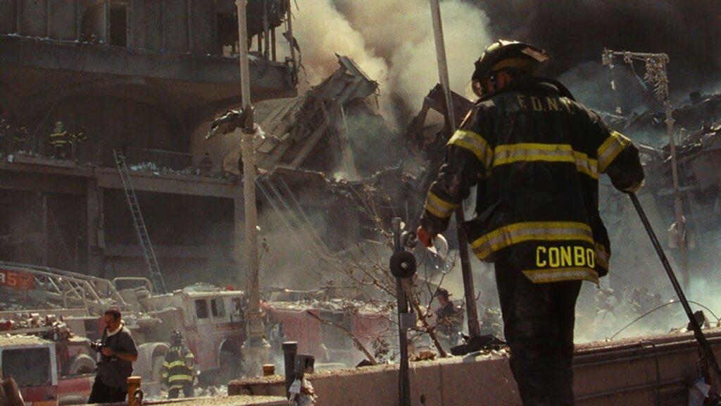 A fire fighter walking across rubble to a NYFD fire truck